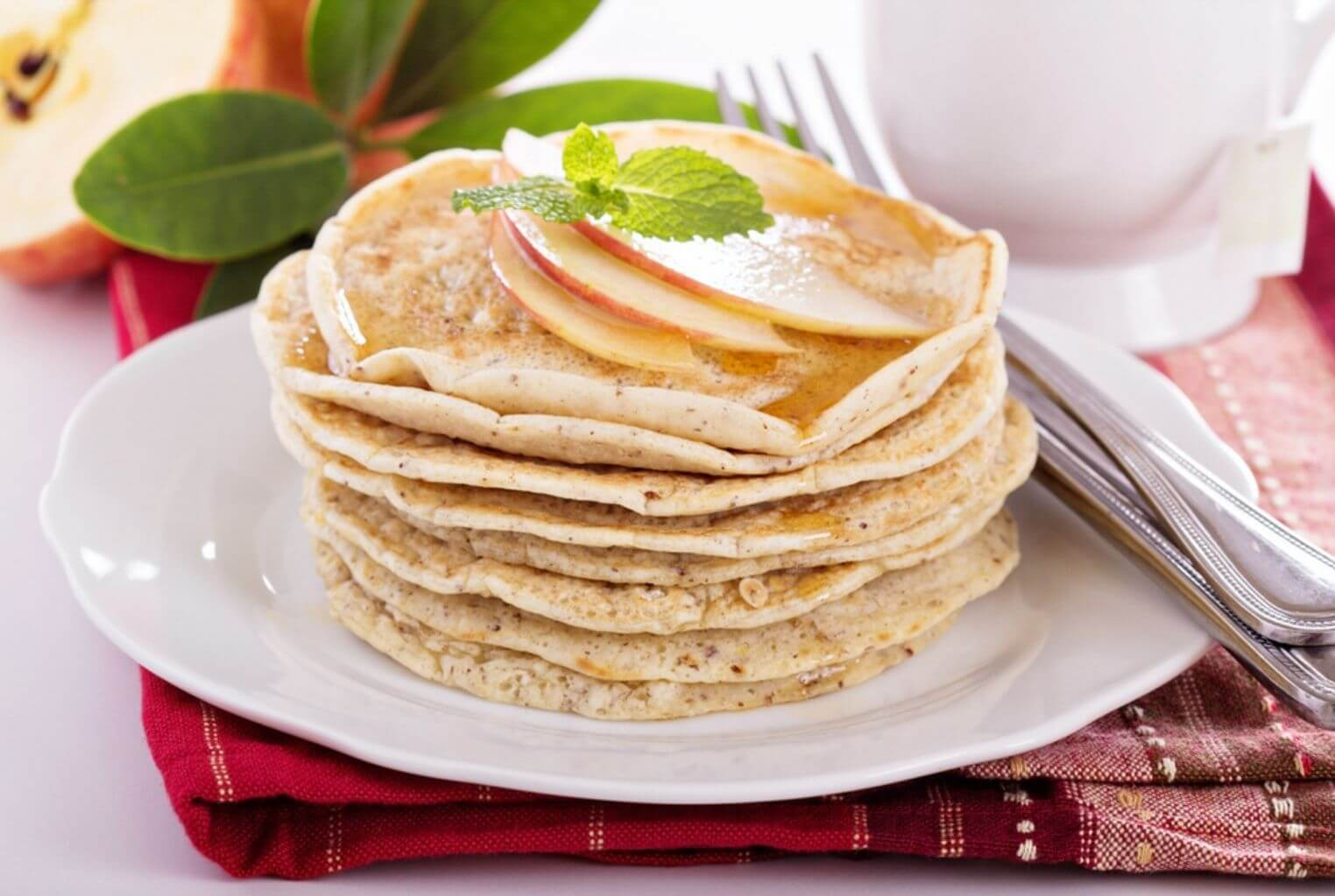 White plate with a stack of thin pancakes garnished with apple slices and mint.