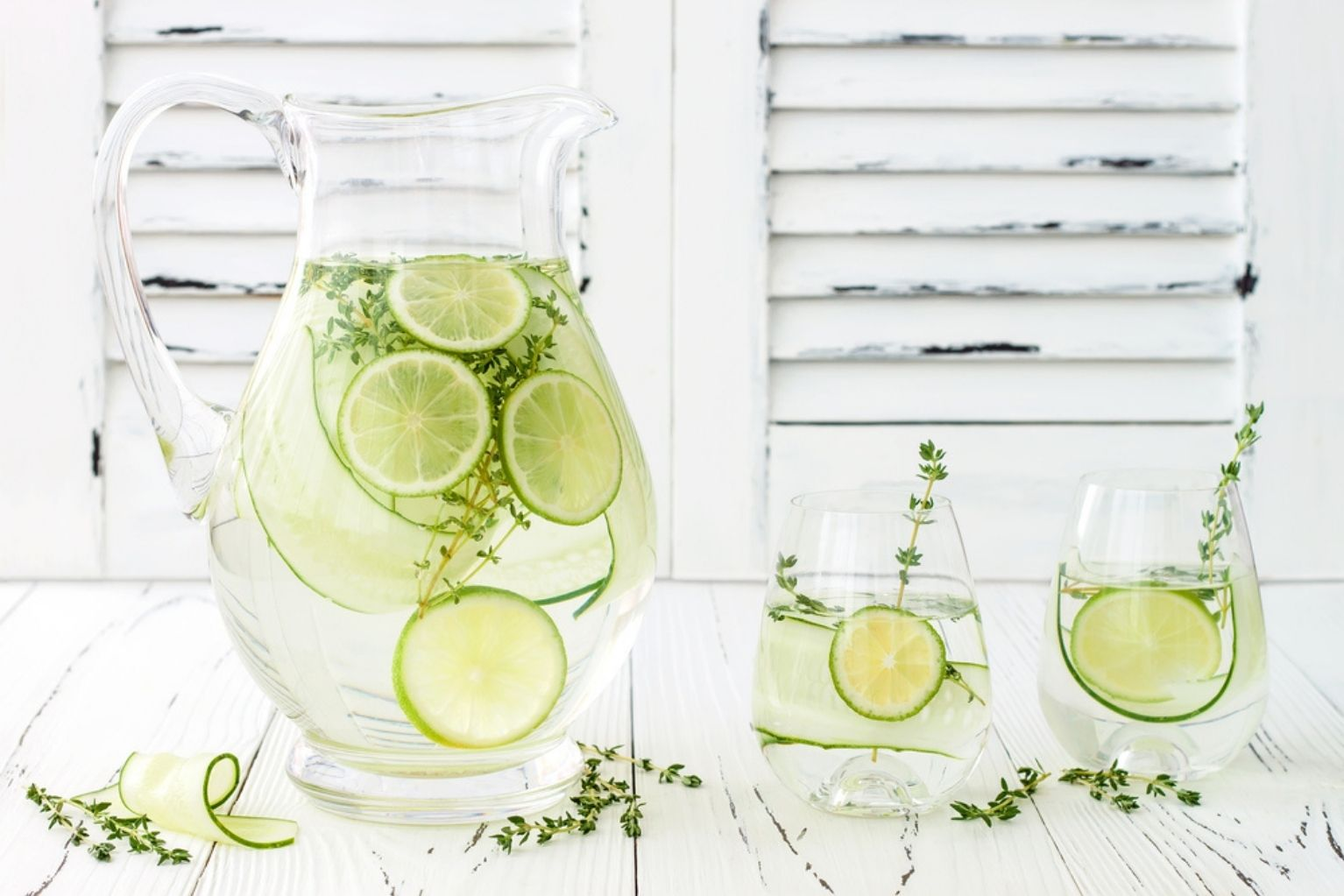 Pitcher of lime and thyme infused water next to two clear glasses full of infused water.
