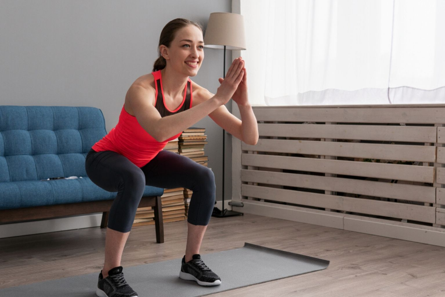 Young athletic woman doing traditional squats in her home