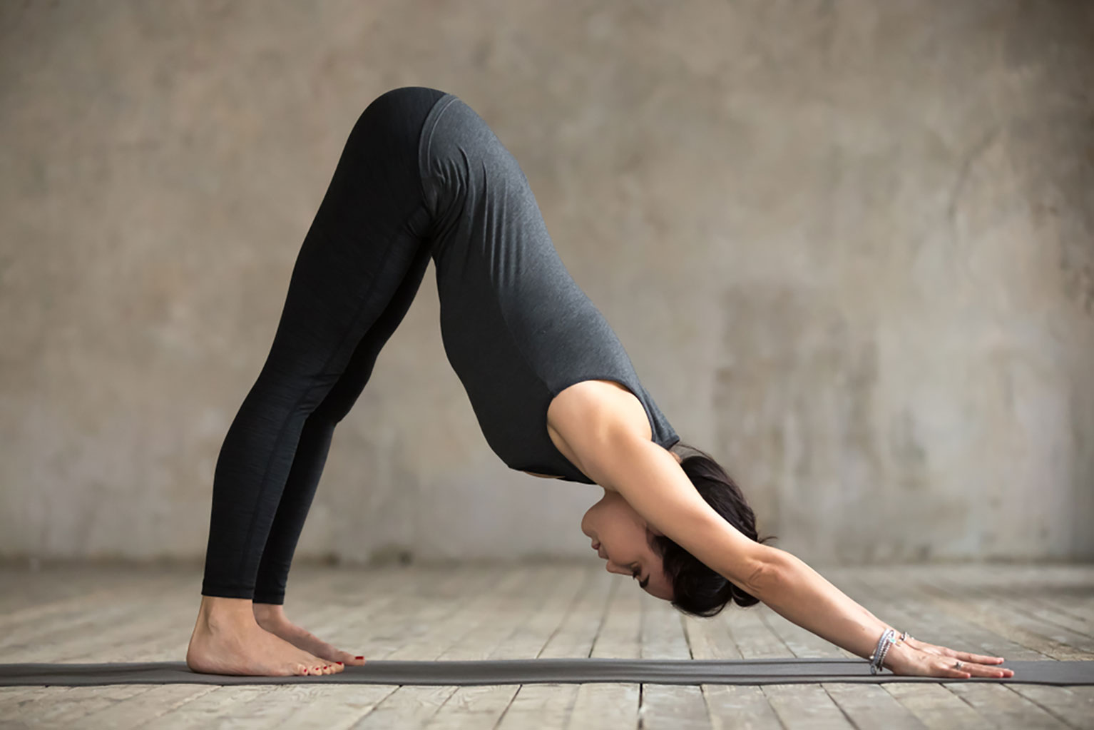Young woman practicing the down dog yoga pose