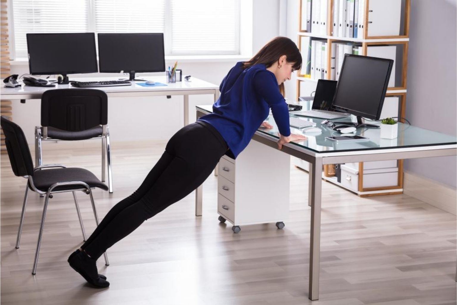 Woman doing a desk push up at her home office
