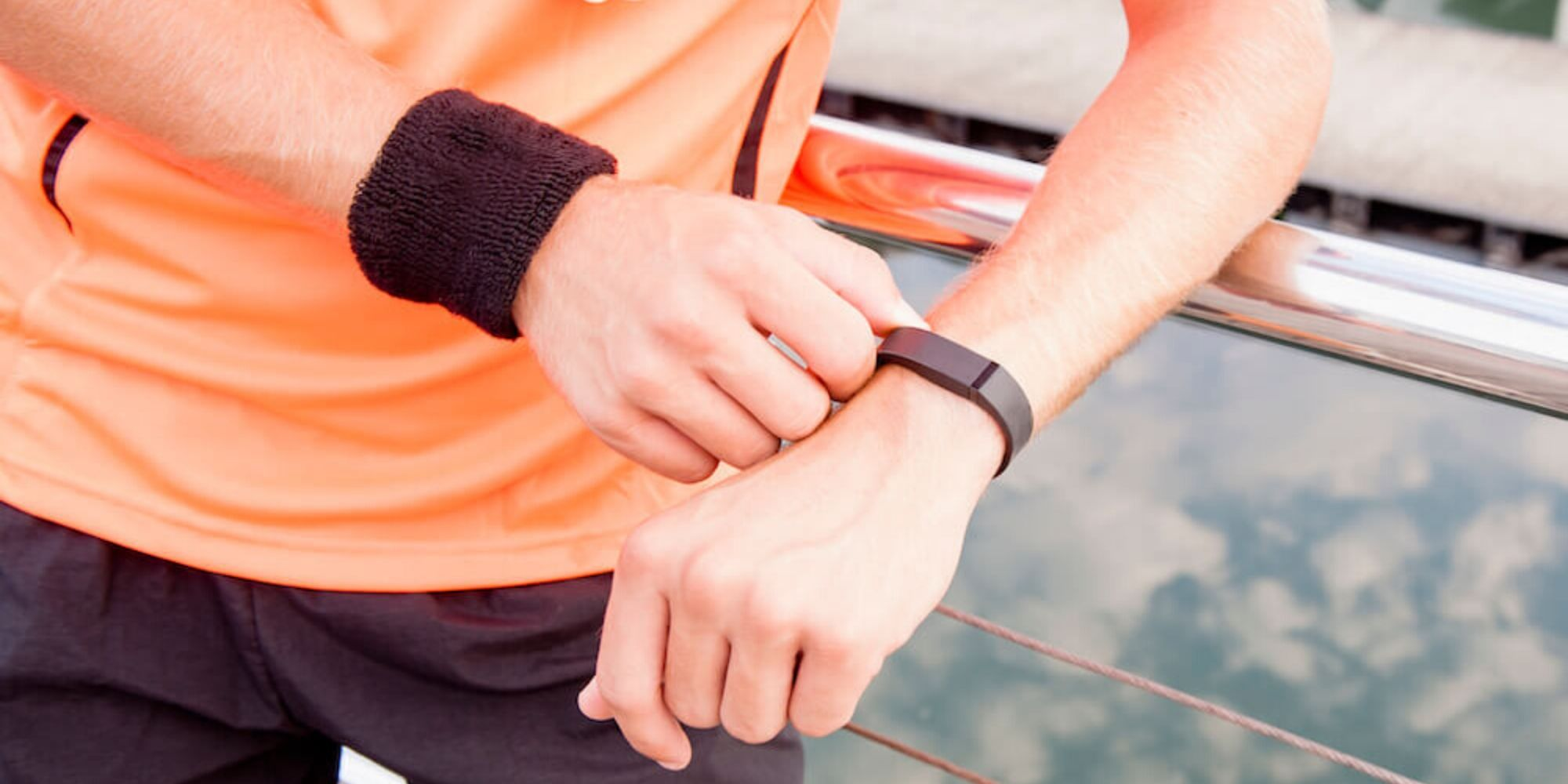 man in an orange shirt checking a fitness watch