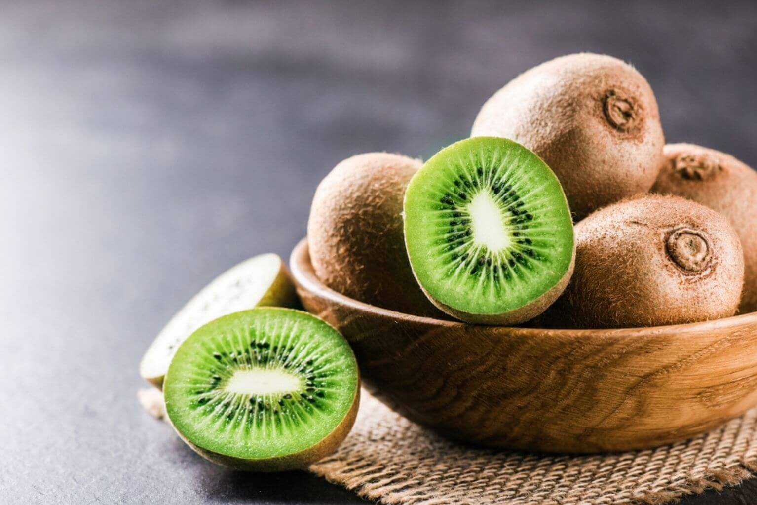 Wooden bowl full of kiwis on a burlap placemat on a wooden table with one kiwi cut in half.