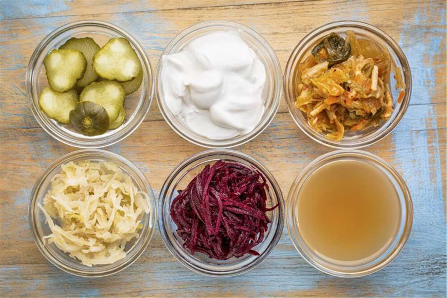 Six jars filled with cucumber pickles, coconut milk yogurt, kimchi, sauerkraut, red beets, and apple cider vinegar