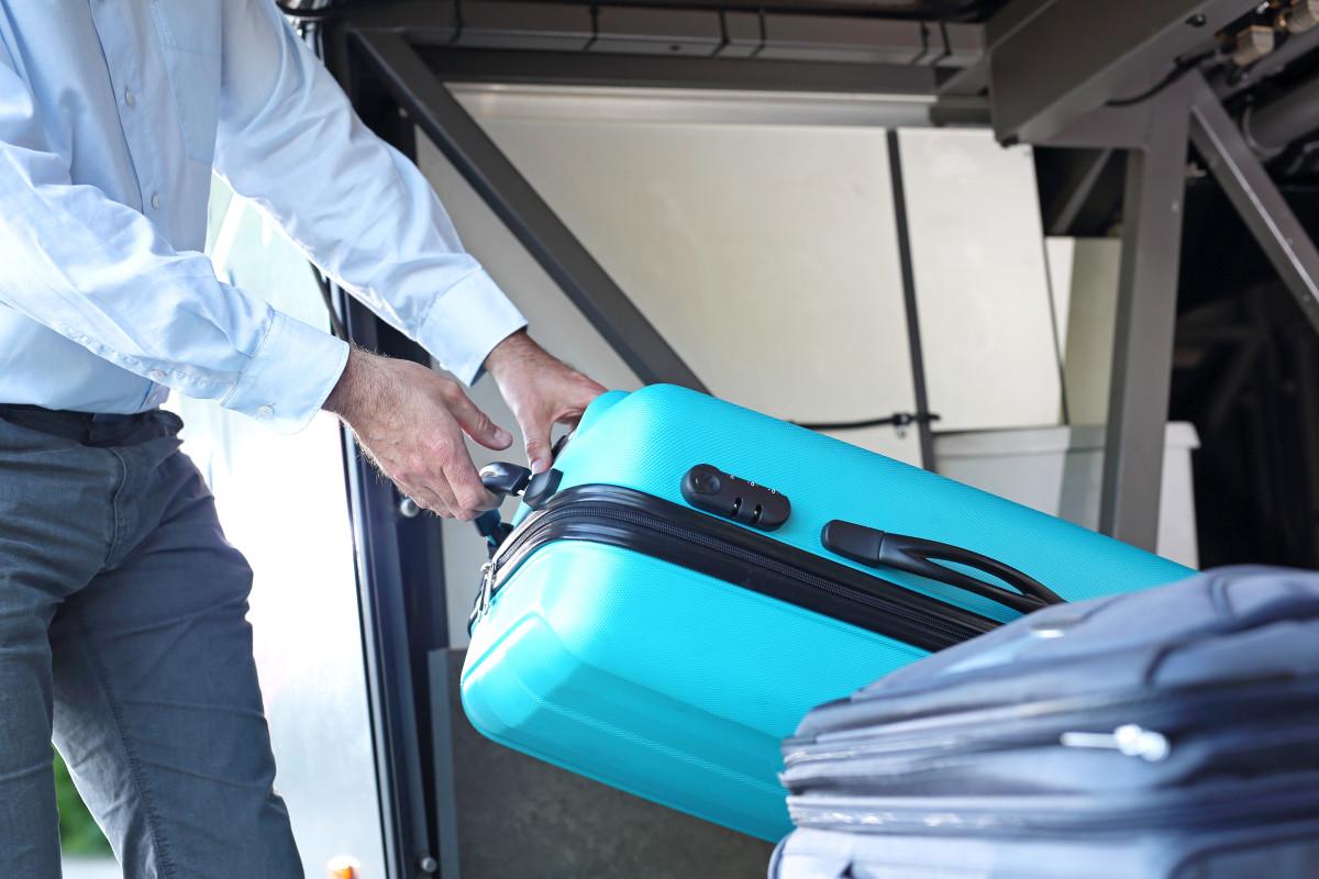 Gepäckmitnahme im Reisebus - Koffer wird aus Bus ausgeladen