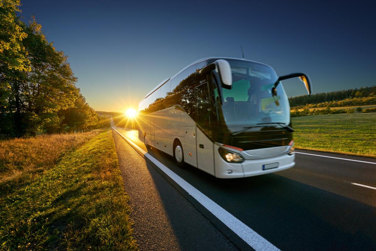 Reisebus mieten mit Snapbus - Bus auf Landstraße bei Sonnenuntergang