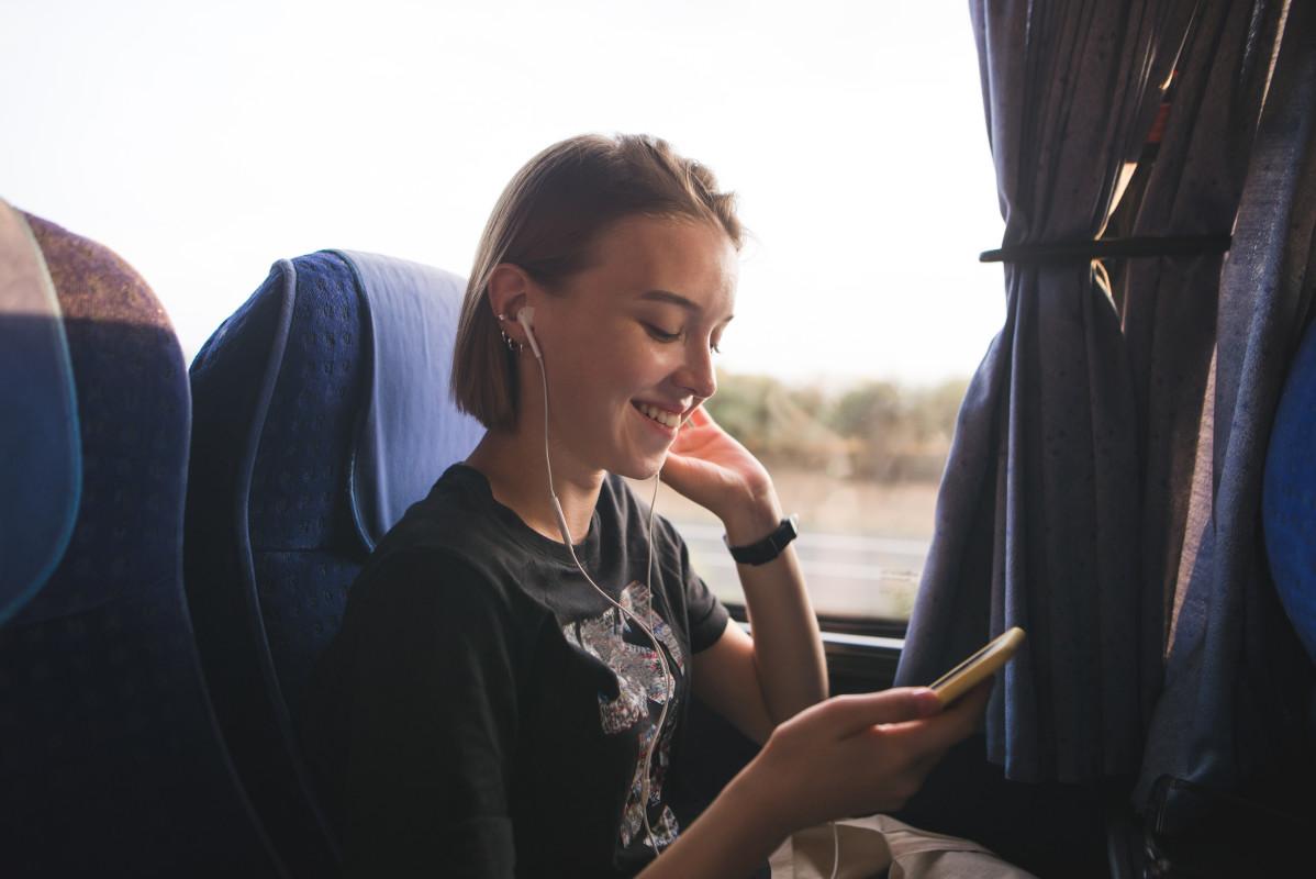 WLAN - Junge Frau mit Handy im Reisebus