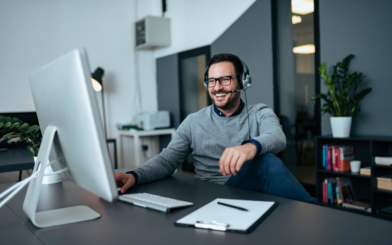 man sitting at computer with headset-scaled