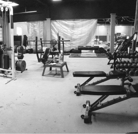 A greyscale picture depicting a smaller gym pictured with a couple benches, a dumbell rack and a cable area