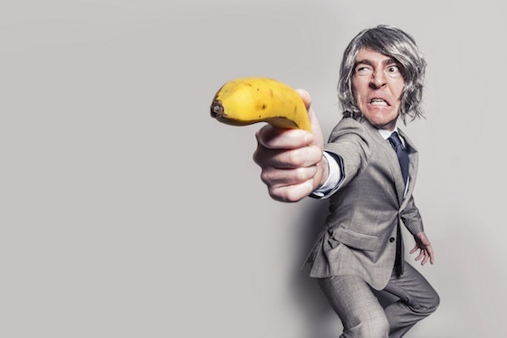 Man in business suit holding a banana
