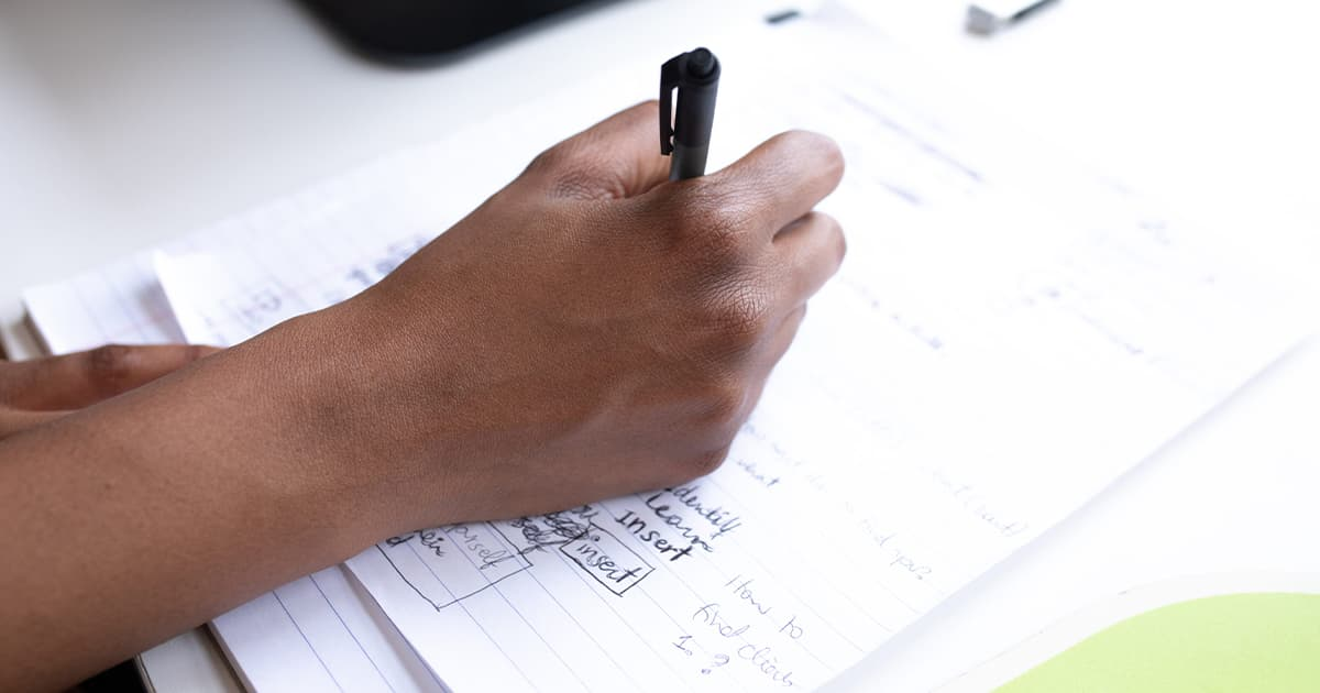 A hand holding a pen writing some plans down on a sheet of paper