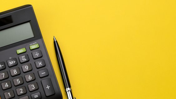 photo of calculator and pen on a yellow background