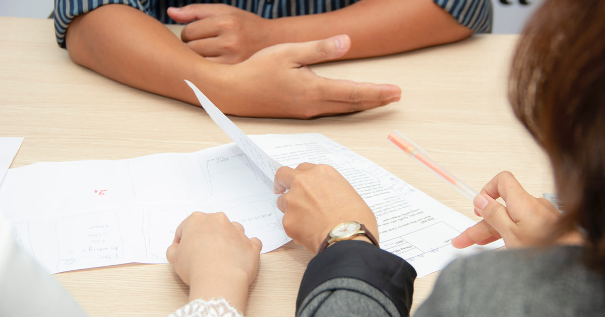 A job interview over a desk, with the hands of the candidate and two interviewers visible over a pile of papers
