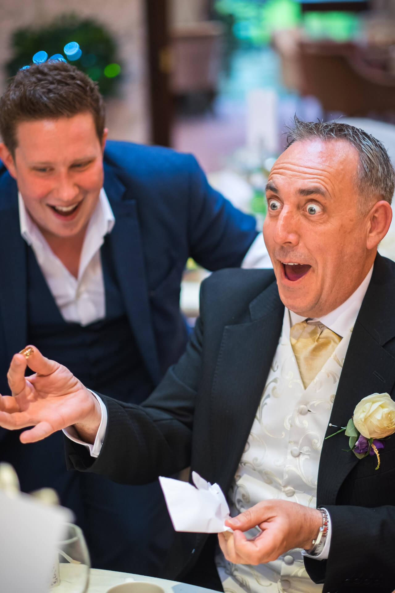Two men at a wedding, one's amazed by a magic trick
