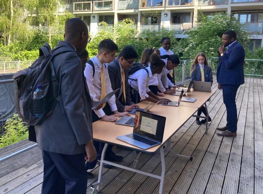 A group of school children along a desk setting up their new laptops