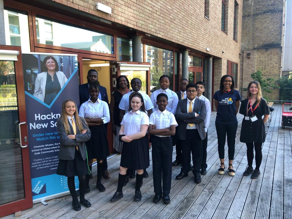 A group of Hackney New School teachers and pupils standing outside on some decking