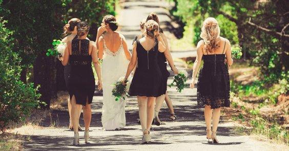 bride and bridesmaids walking down green path