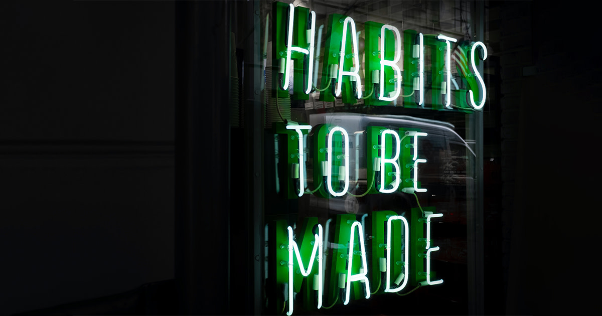 """A green neon sign that says """"Habits to be made"""""""