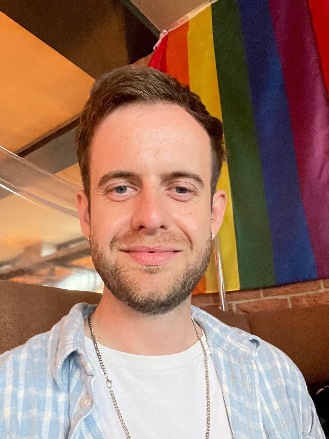 Photo of a man wearing a blue shirt, a rainbow flag behind him