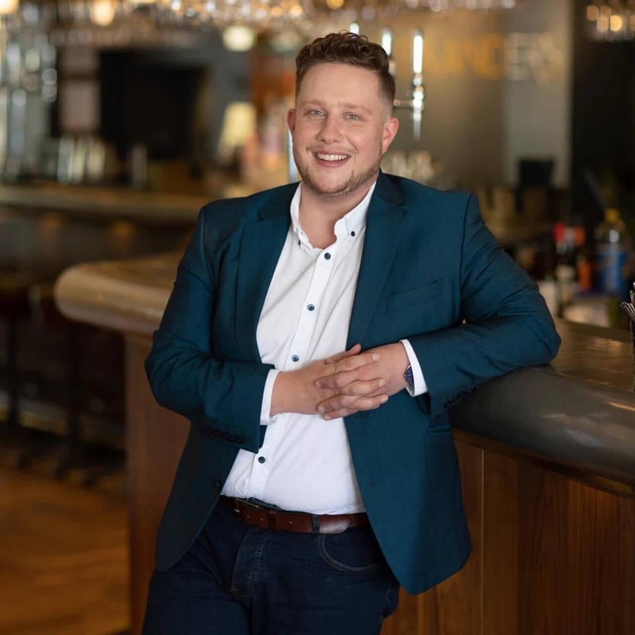 Man in a blazer, leaning against a bar