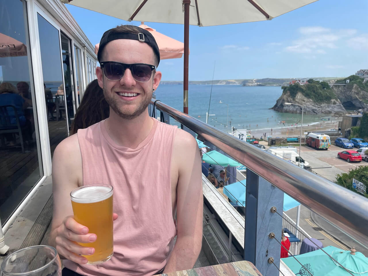 Man sitting on a sunny balcony with a pint