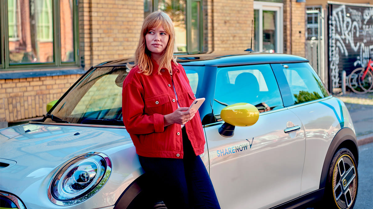 mini-electric-woman-leaning-car
