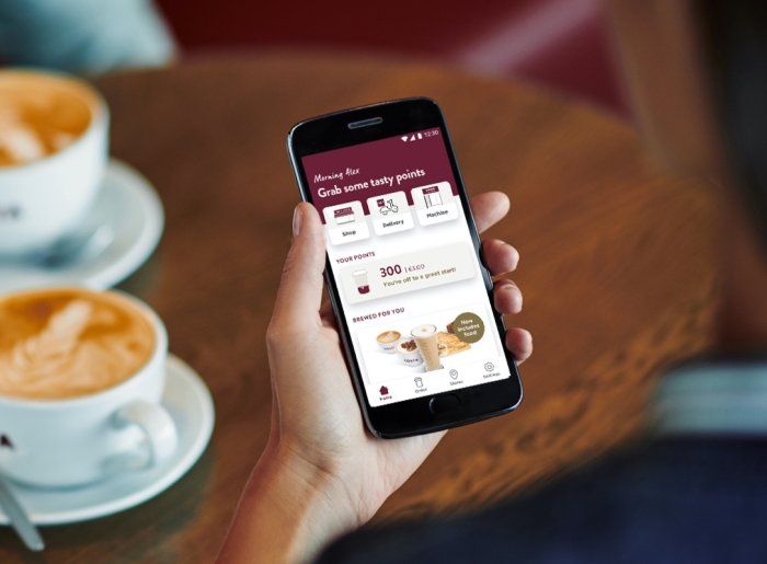 Costa Coffee customer holding a mobile phone with the Costa app displayed