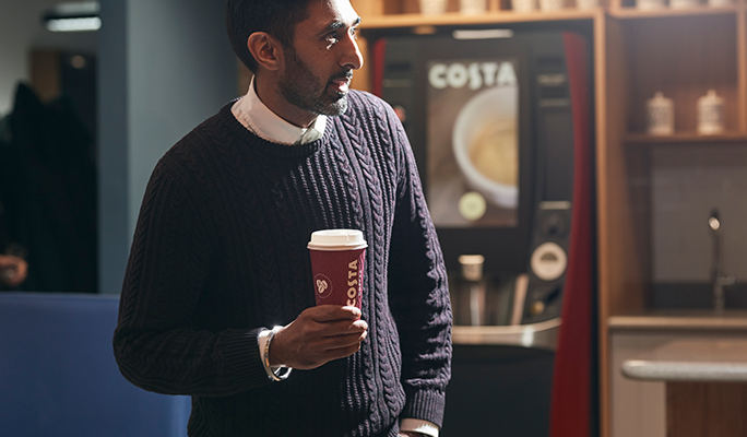 Costa Express customer with coffee
