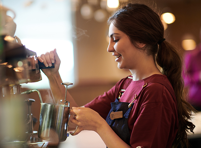A Costa Coffee Barista steaming milk