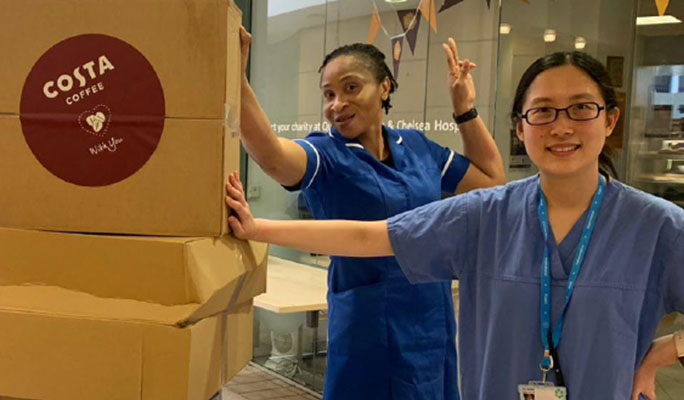 Two NHS nurses standing next to a box of Costa Coffee Ready-to-Drink cans that have been delivered.