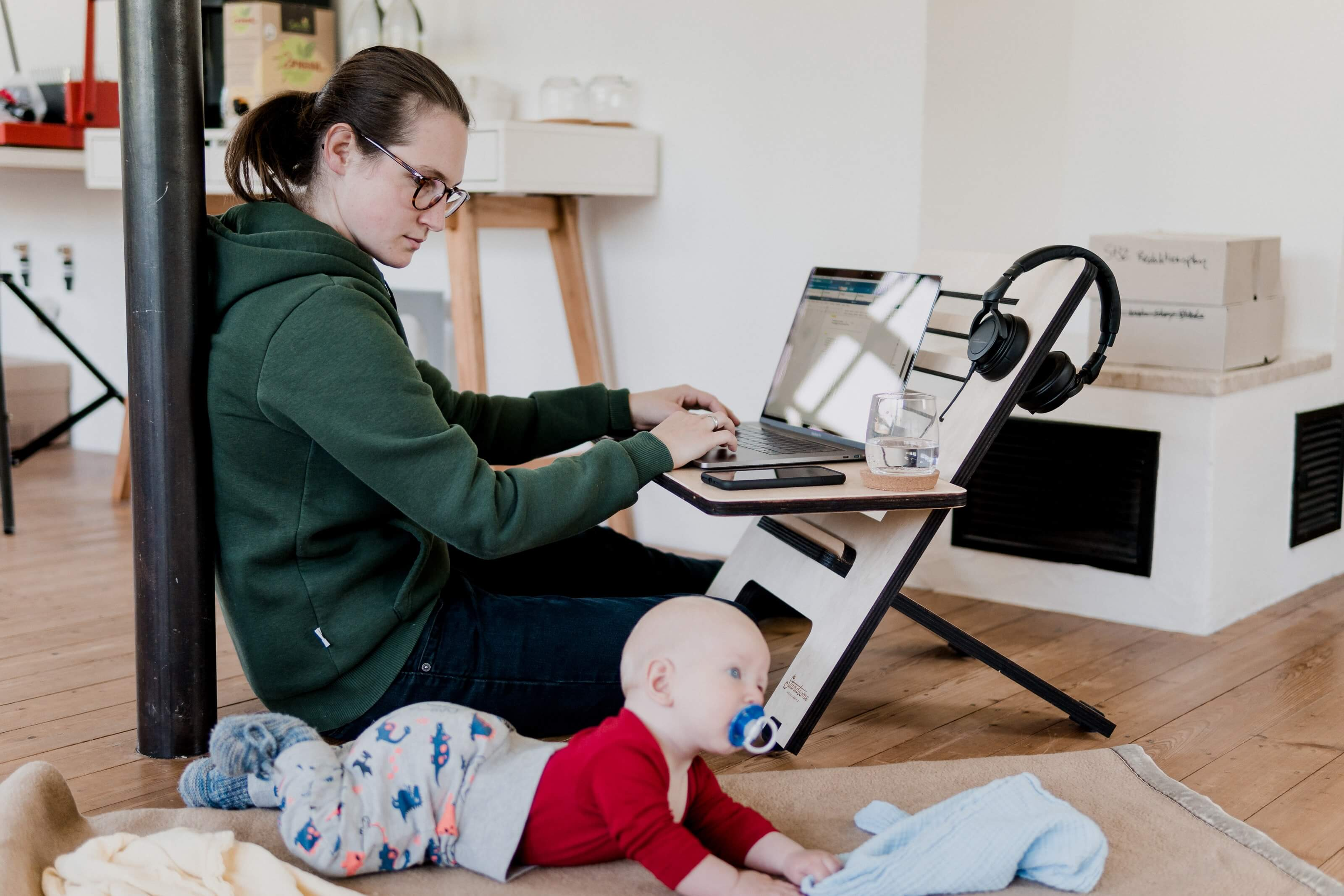 A woman working from home and looking after her baby at the same time