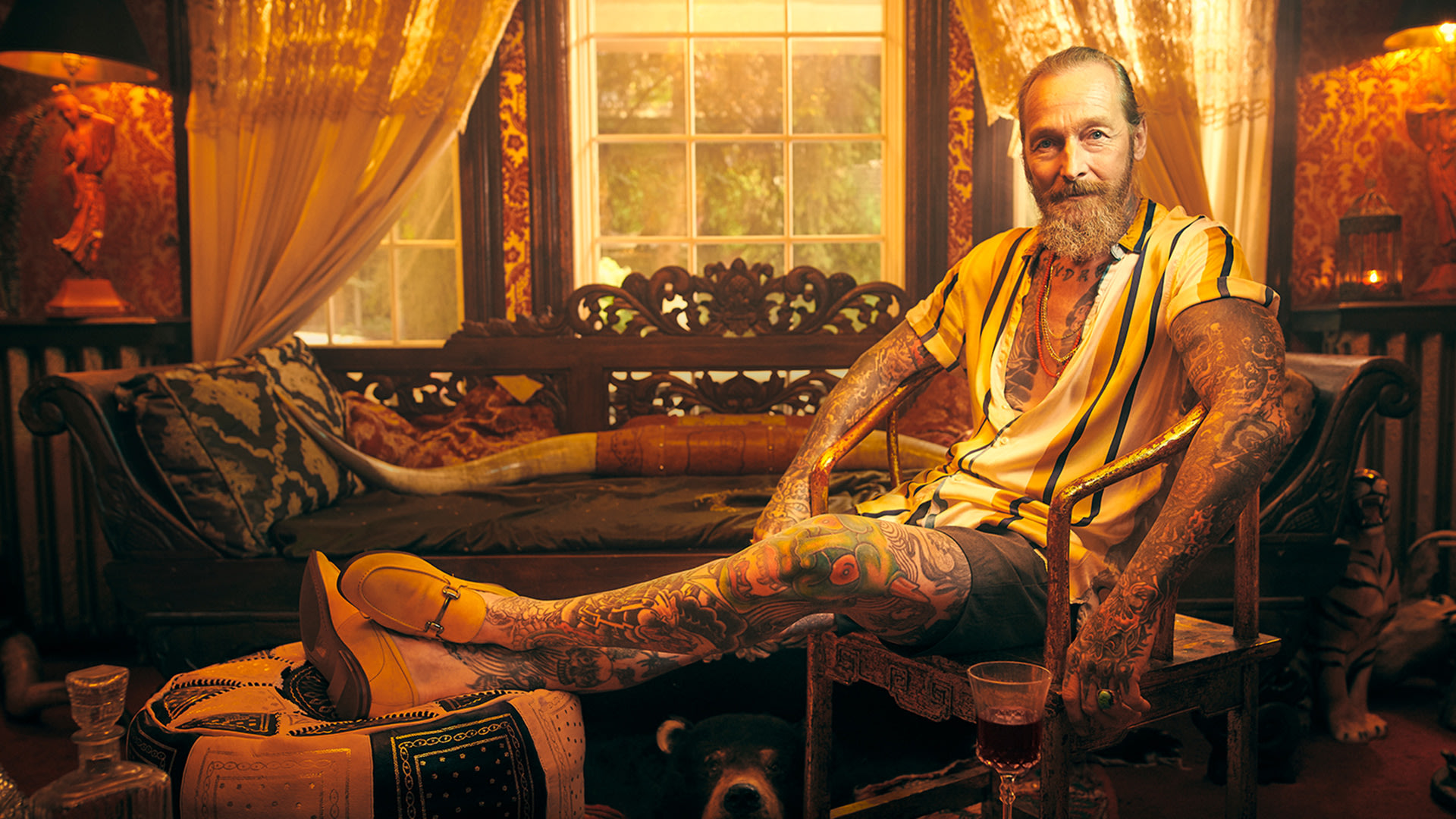 Allen showing his tattoos in an armchair in a living room