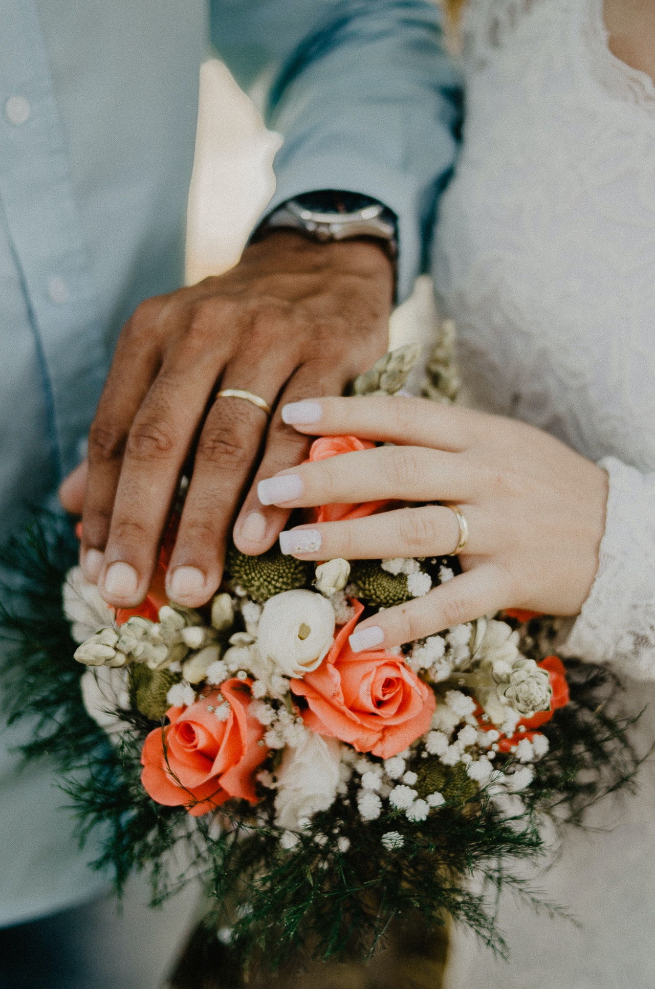 man and woman-s hand on bouquet