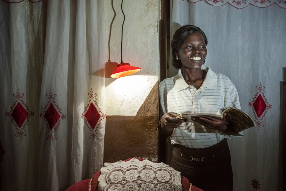 A woman smiles because she has solar-powered electricity