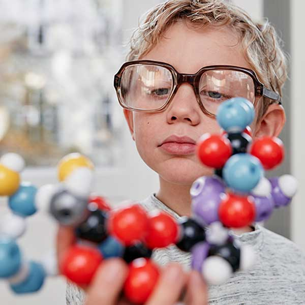 A child scientist looks at the molecular model
