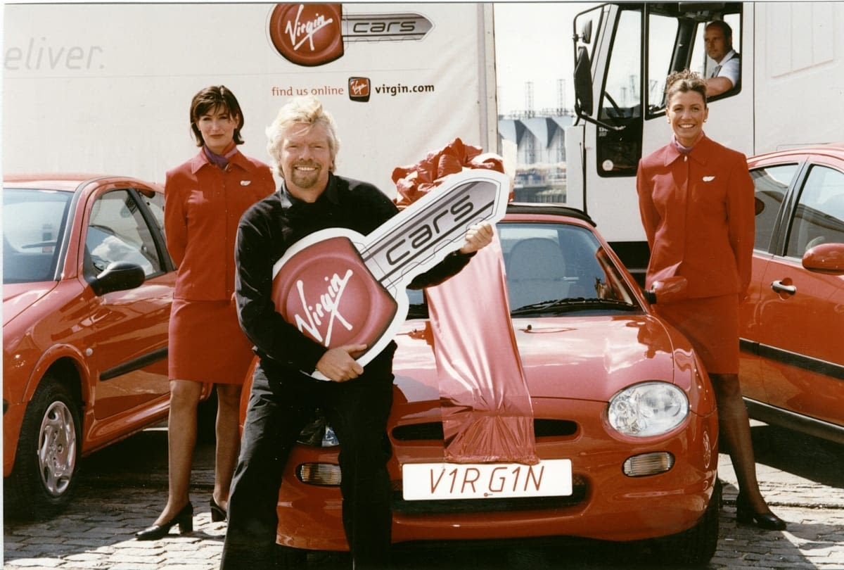 Richard Branson in front of red cars with a cardboard key with 'Virgin Cars' written on it