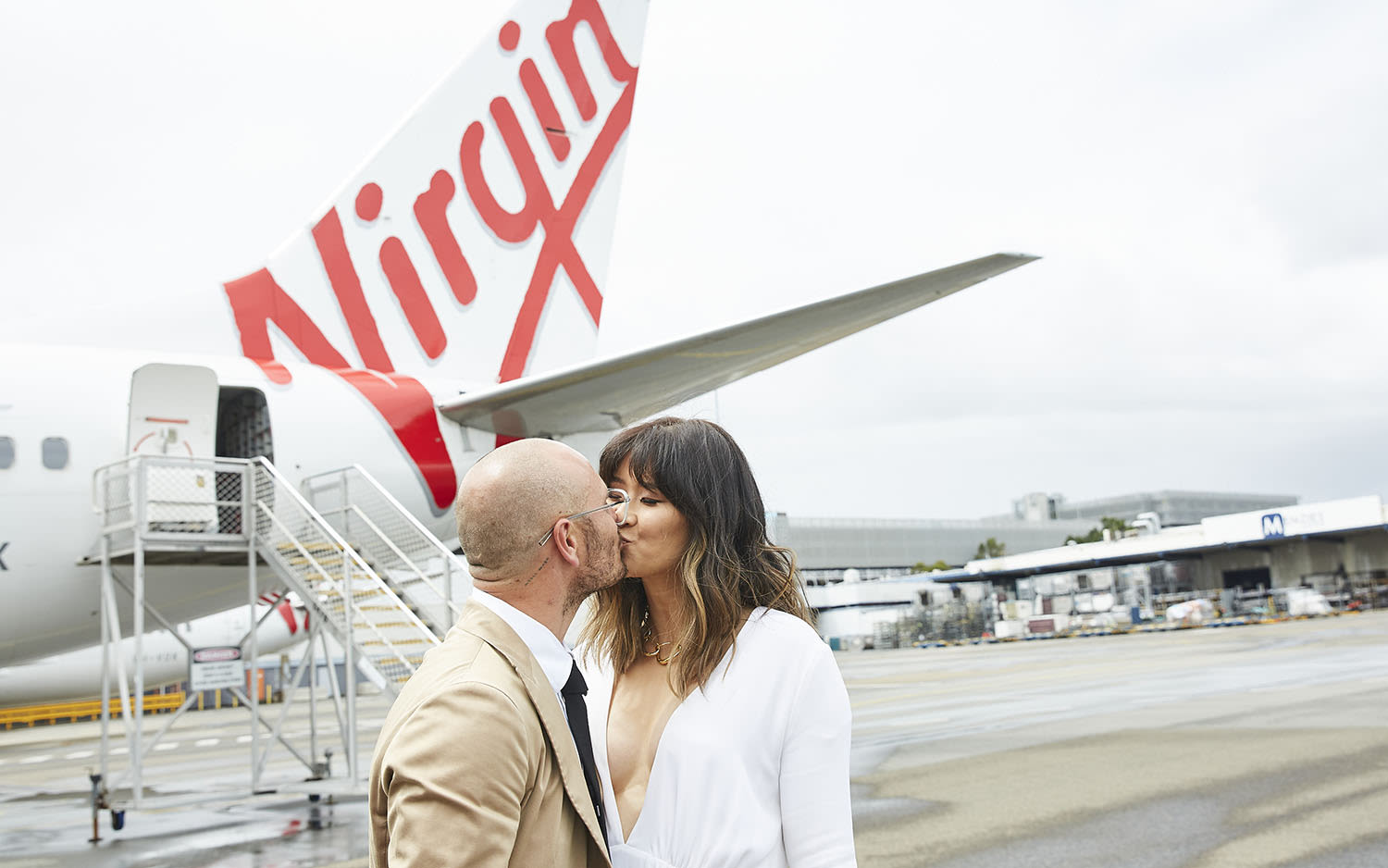 Luke and Elaine Serdar share a kiss outside a Virgin Australia aircraft after their onboard wedding