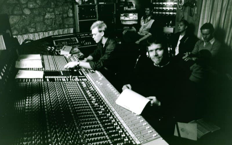A black and white image of a young Richard Branson in a sitting in a recording studio