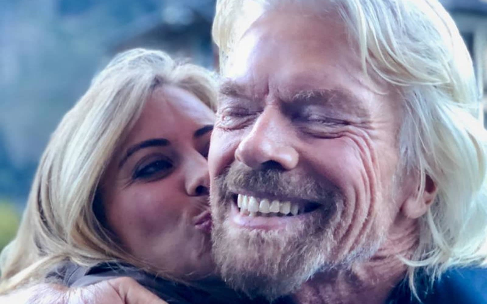 Close up of Richard and Holly Branson as Holly gives Richard a kiss on the cheek