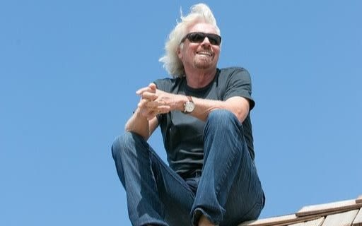 Richard Branson sitting on the roof on Necker Island