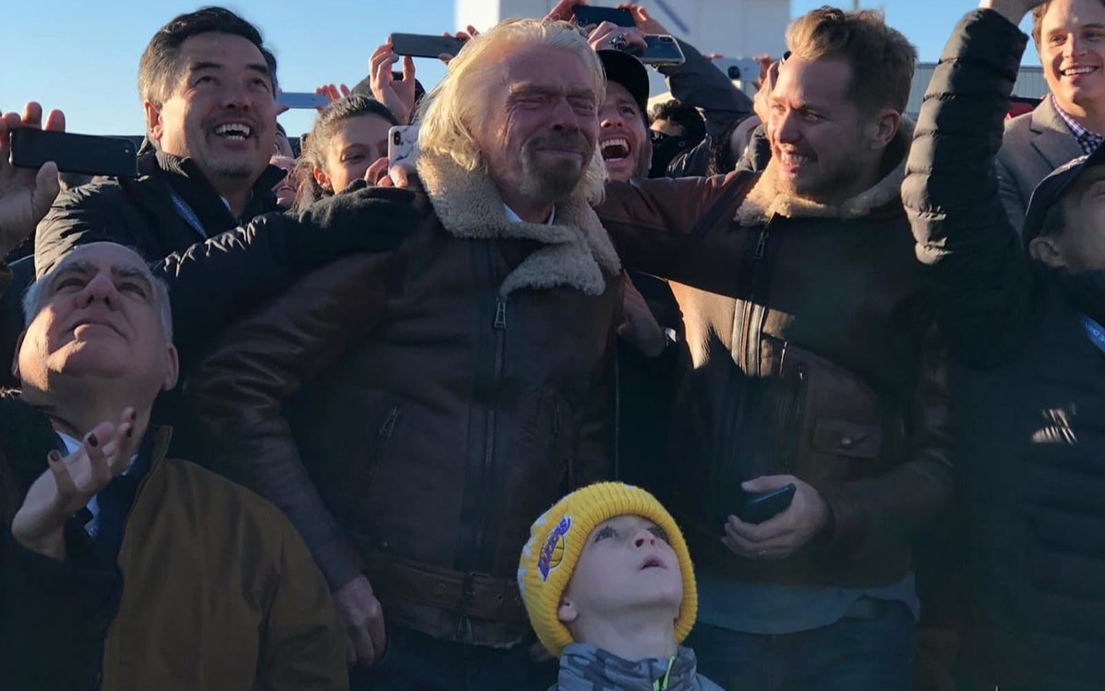 Richard Branson and Sam Branson celebrate with a crowd during Virgin Galactic's first spaceflight