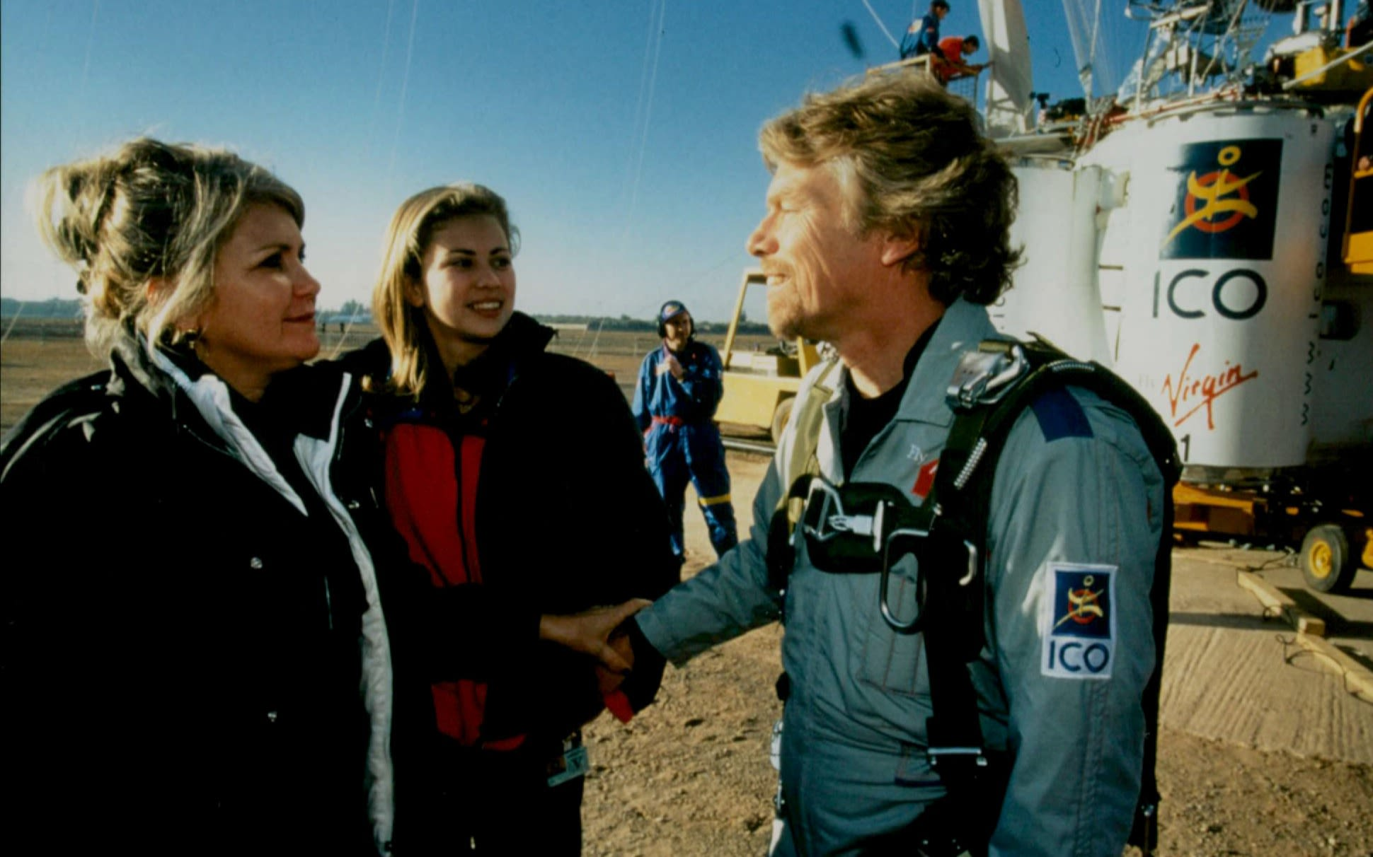 Richard Branson speaking to Joan Branson and Holly Branson in front of a hot air balloon