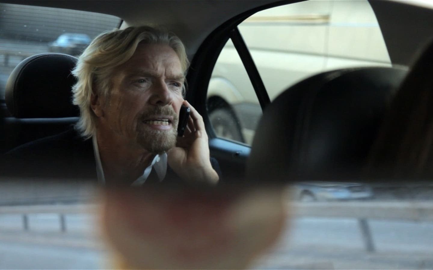 Richard Branson sitting in the back of a car on the phone