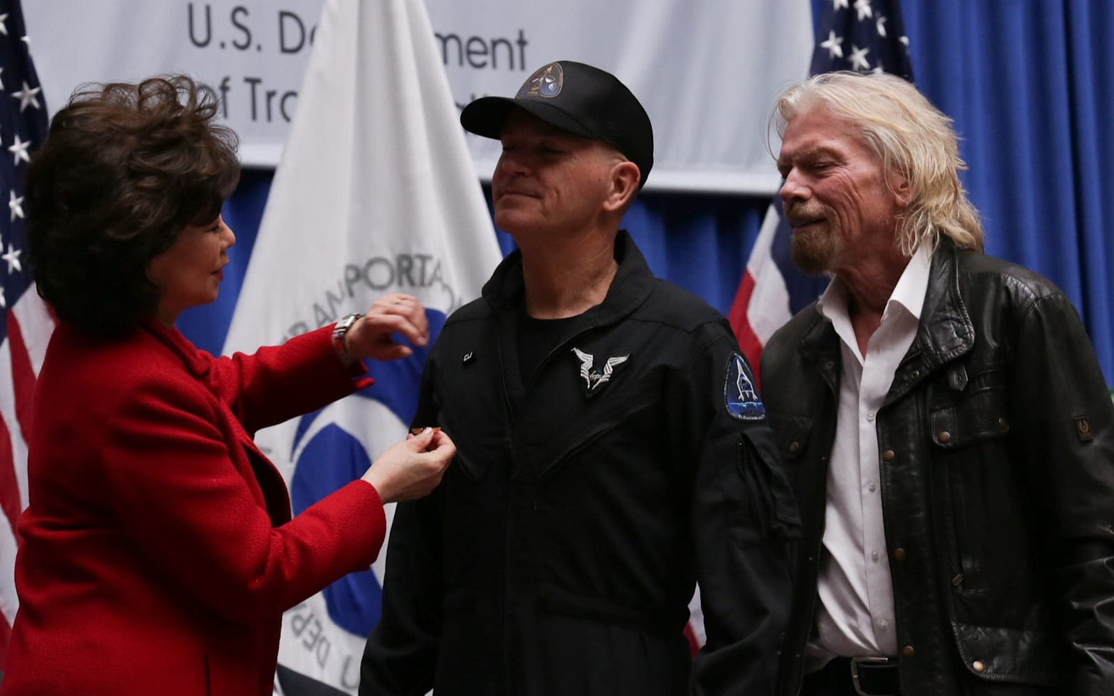 Richard Branson stands with Virgin Galactic pilot CJ Sturckow as he receives his Commercial Astronaut Wings from Elaine Chao