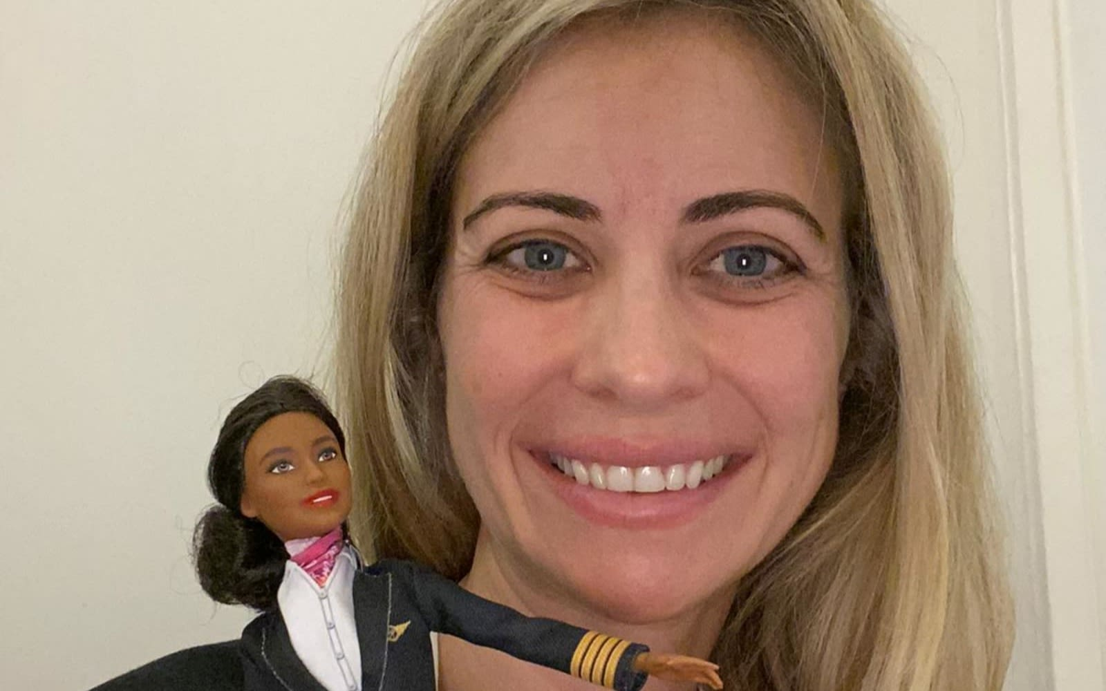 Holly Branson smiling, holding a Barbie doll dressed in a pilot's uniform