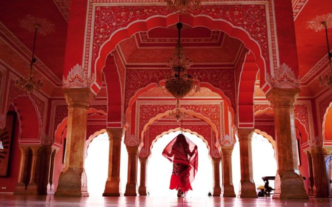 A woman dressed in red inside an Indian temple