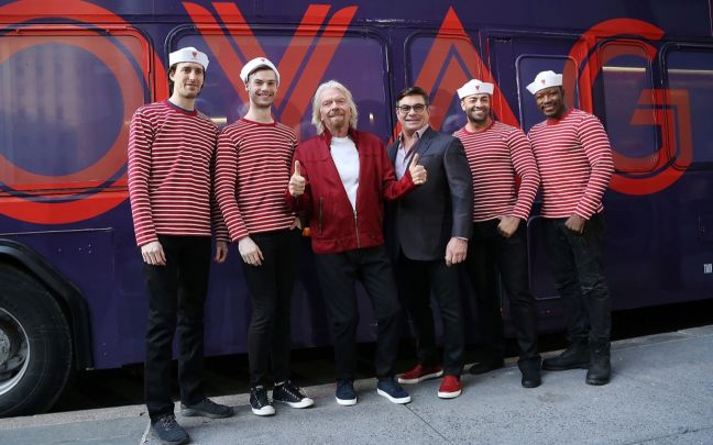 Richard Branson and Virgin Voyages CEO Tom McAlpin stand in front of a bus that says Virgin Voyages with Virgin Voyages crew members