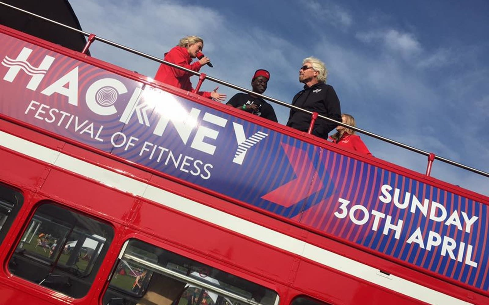 Richard Branson with the hosts of Virgin Sport Hackney on the roof of a bus