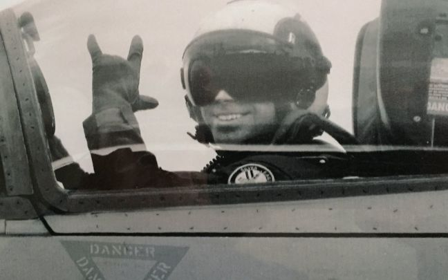 Virgin Galactic pilot Patrick Moran waves form inside a military aircraft