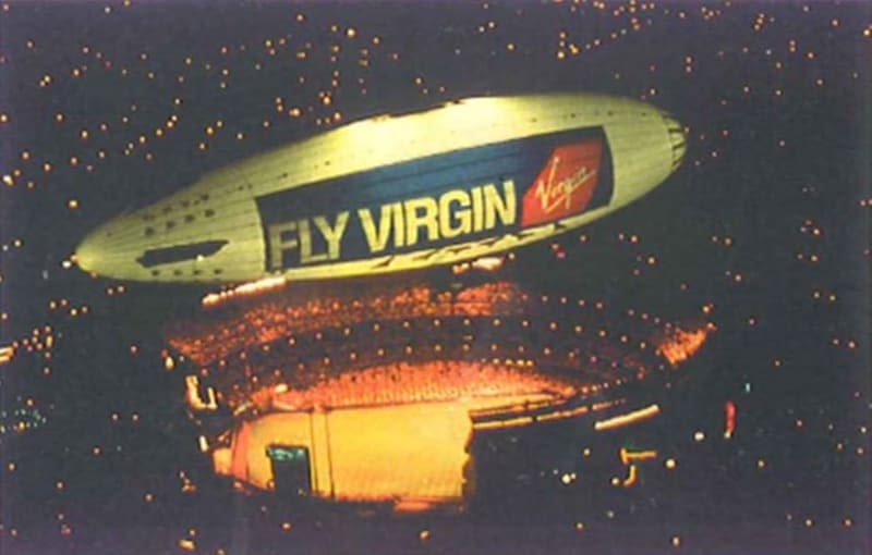 An airship with the text Fly Virgin and the Virgin logo on it flying above a stadium